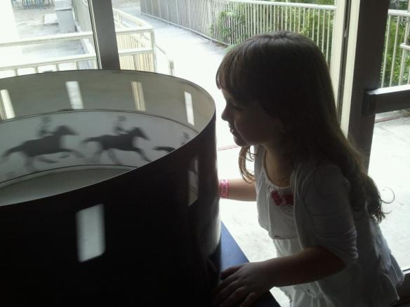 Madison looking into a zoetrope.